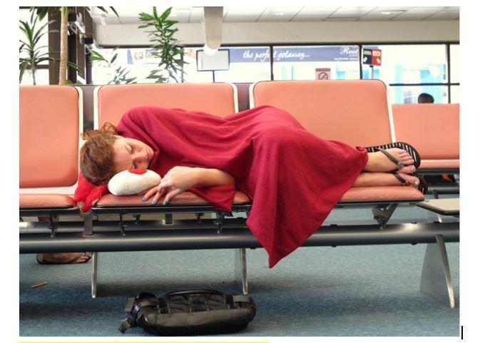 девушка спит на сиденьях в аэропорту